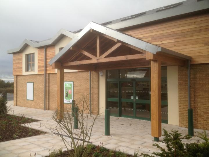 Oak entrance porch canopy clad with cedar for large national pet store